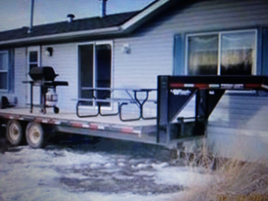 flatbed trailer next to mobile home